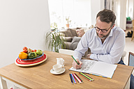 Man sitting at wooden table with colouring book and coloured pencils - BOYF000284