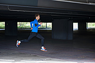 Young sporty man jogging with smartwatch and headphones - DIGF000243