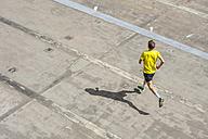 Young man jogging, concrete floor - DIGF000249