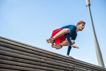 Young sporty man jumping over a bench - DIGF000258