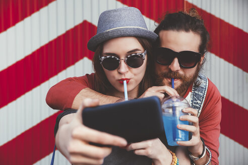 Young couple with soft drinks taking selfie with smartphone - RTBF000112