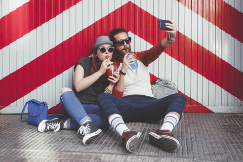 Young couple with soft drinks taking selfie with smartphone - RTBF000115