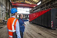 Manager and worker talking at container in factory hall - DIGF000267
