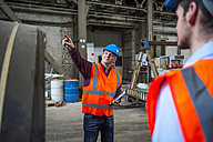 Man with safety vest in factory hall pointing his finger - DIGF000276