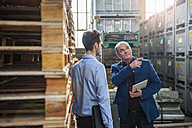 Manager talking to colleague between pallets - DIGF000297