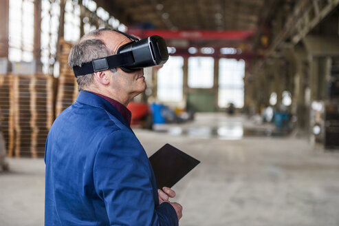 Manager standing in factory hall looking through VR glasses - DIGF000303