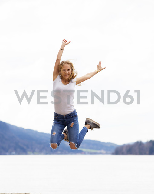 Austria, portrait of happy teenage girl jumping in the air - WWF003939