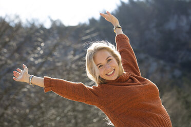 Portrait of happy teenage girl with raised arms - WWF003942
