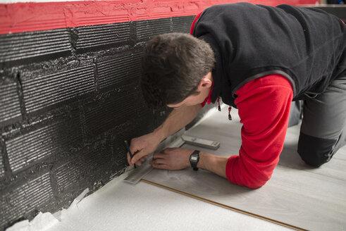 Young man placing a laminate floor - RAEF001048