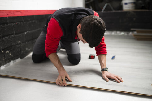 Young man placing a laminate floor - RAEF001051