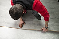 Young man placing a laminate floor - RAEF001054