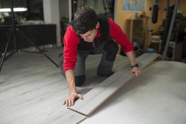 Young man placing a laminate floor - RAEF001057