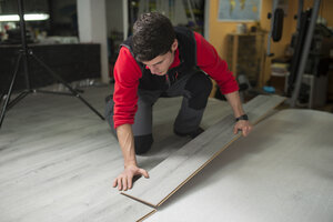 Young man placing a laminate floor - RAEF001057