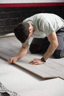 Young man placing a laminate floor - RAEF001066