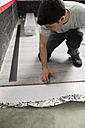 Young man placing a laminate floor - RAEF001069