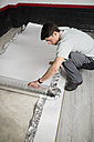 Young man placing a insulating material for a laminate flooring - RAEF001072