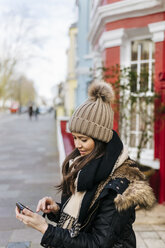 UK, London, Notting Hill, young woman looking at her smartphone - MGOF001721