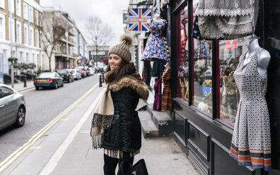 UK, London, Notting Hill, smiling young woman on shopping tour - MGOF001724