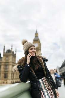 UK, London, happy young woman telephoning with smartphone in front of Palace of Westminster - MGOF001727