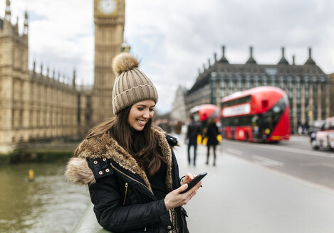 UK, London, smiling young woman looking at her smartphone in front of Palace of Westminster - MGOF001730