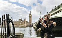 UK, London, young woman blowing soap bubbles - MGOF001733
