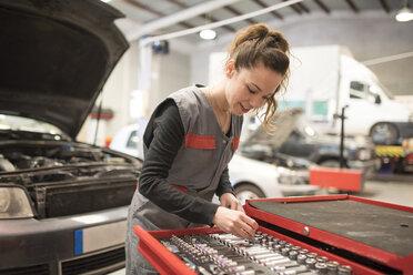 Woman working in workshop, taking tool - JASF000658