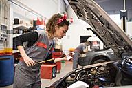 Mechanics working in workshop, checking oil level - JASF000664