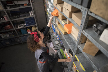 Woman in warehouse, she taking a box from shelf - JASF000685