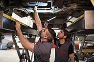 Mechanics working under car with led lights - JASF000697