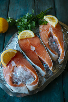 Raw salmon fillets with lemon and parsley on a plate with ice - KIJF000321