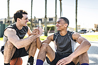 Two young men shaking hands on outdoor basketball court - LEF000098