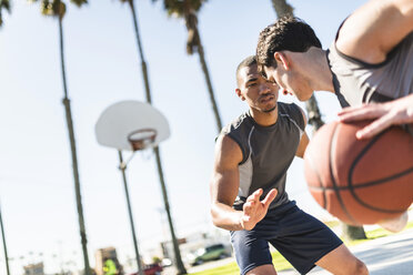 Two young men playing basketball on an outdoor court - LEF000104