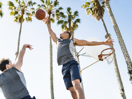 Two young men playing basketball on an outdoor court - LEF000107