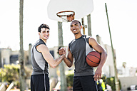 Two young men shaking hands on outdoor basketball court - LEF000115