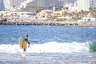 Spain, Tenerife, boy with surfboard in the sea - SIPF000358
