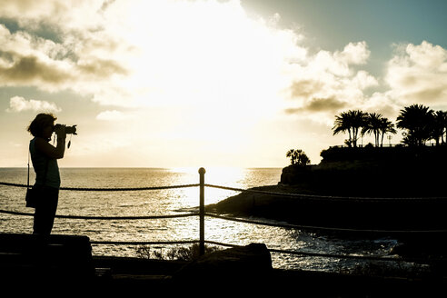 Spain, Tenerife, woman taking a picture at the ocean at sunset - SIPF000361