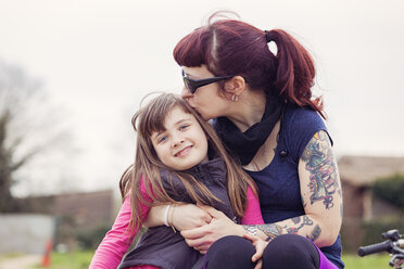 Tattooed woman kissing her smiling little daughter - XCF000078