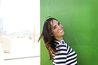 Portrait of happy woman at green wall - VABF000454