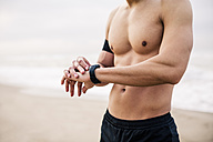 Sportive young man on the beach adjusting watch - EBSF001313