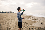 Sportive young man drinking from bottle on the beach - EBSF001316