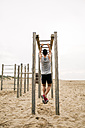 Young man exercising on monkey bars on the beach - EBSF001325