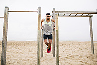 Young man exercising on bars on the beach - EBSF001328