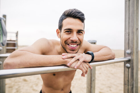 Portrait of smiling athlete on bars on the beach - EBSF001331