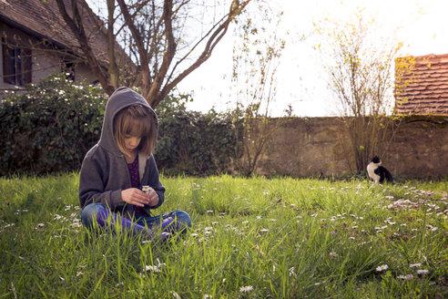 Girl wearing hooded jacket sitting on flower meadow - LVF004777