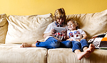 Two smiling boys sitting on couch using digital tablet - MGOF001741