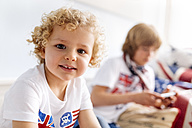Portrait of relaxed little boy at home with his brother in the background - MGOF001759