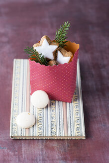 Paper bag with nuts and Christmas cookies on a book - MYF001451