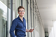 Portrait of young businessman with  digital tablet in front of an office building - DIGF000312