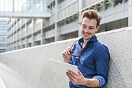 Portrait of young businessman  leaning against wall looking at   digital tablet - DIGF000318