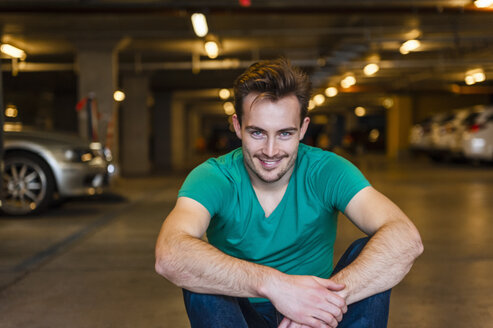 Portrait of smiling young man sitting in underground car park - DIGF000324